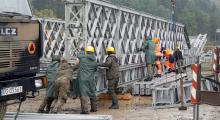 W strugach deszczu nasuwali przęsło wojskowego mostu na Kamienicy